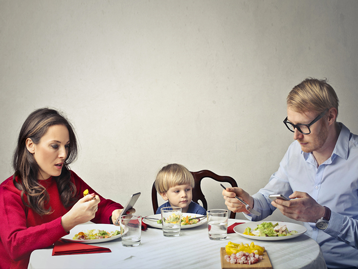 Mother and father using technology at dinner table, while ignoring thier young child with them