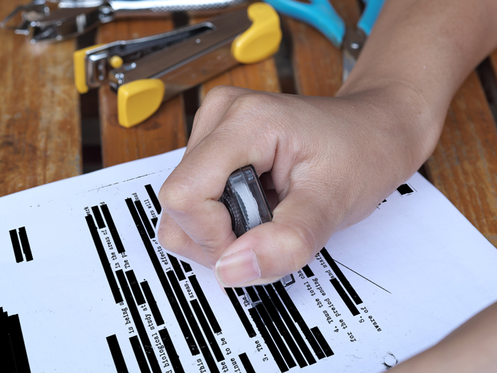 woman using a blackout roller to black out text on paper
