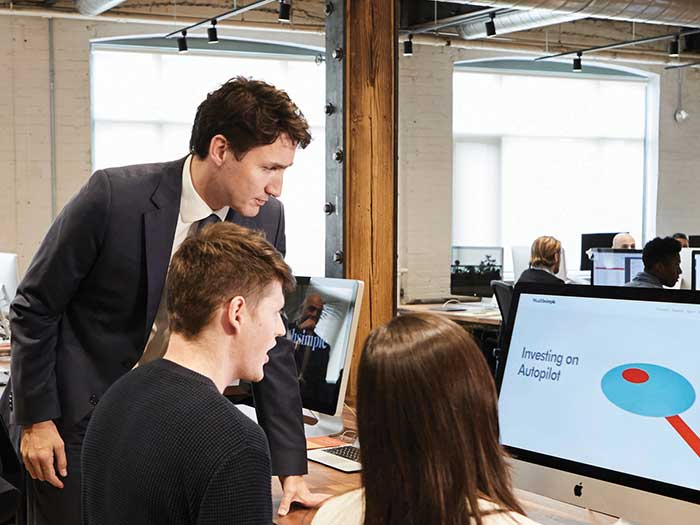 PM Justin Trudeau, looking over the shoulder of a Wealthsimple employee, at a computer screen