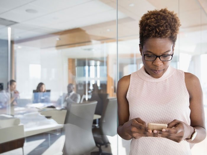 Businesswoman texting with cell phone outside conference room meeting