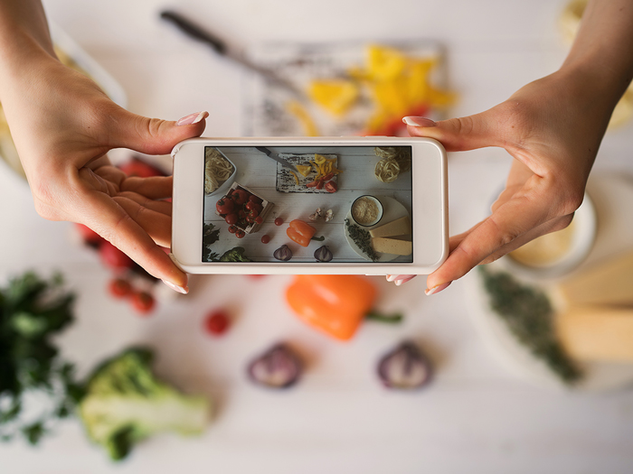 Hands with the phone close-up pictures of meal. Young woman, cooking blogger is cooking at the home kitchen in sunny day and is making photo at smartphone. Instagram food blogger workshop concept.
