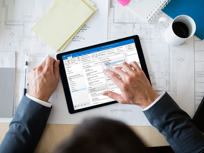 Overhead view of business man using Outlook program on his tablet, at his office desk