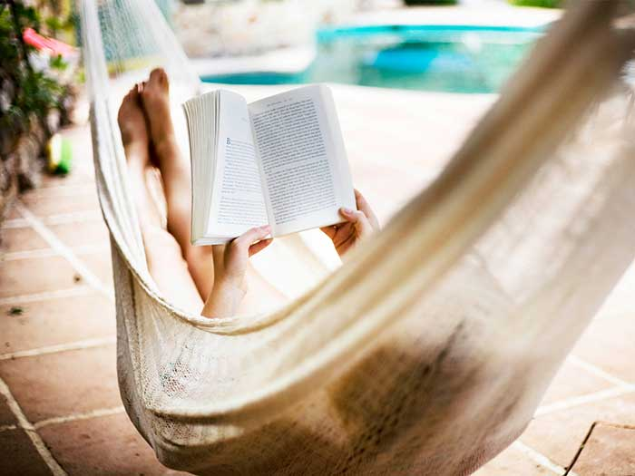 Woman reading a book while in a hammock