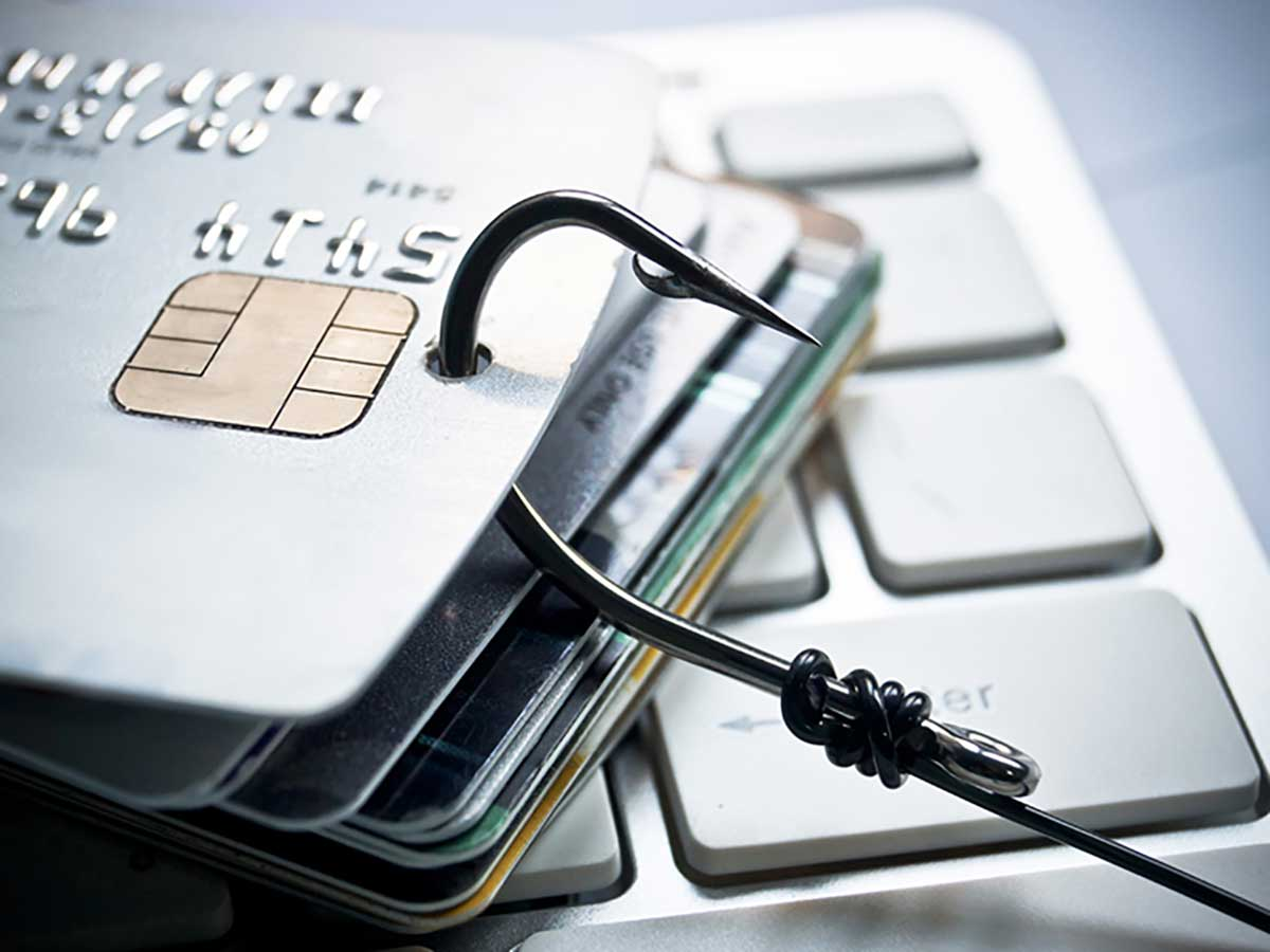 Stack of credit cards on computer keyboard, hooked with a sharp fishing hook
