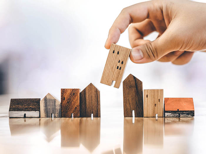 Hand choosing mini wooden house model from a row of wooden buildings