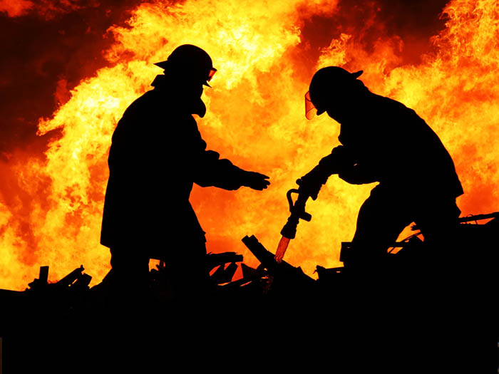 Silhouette of two firemen fighting a huge fire behind them