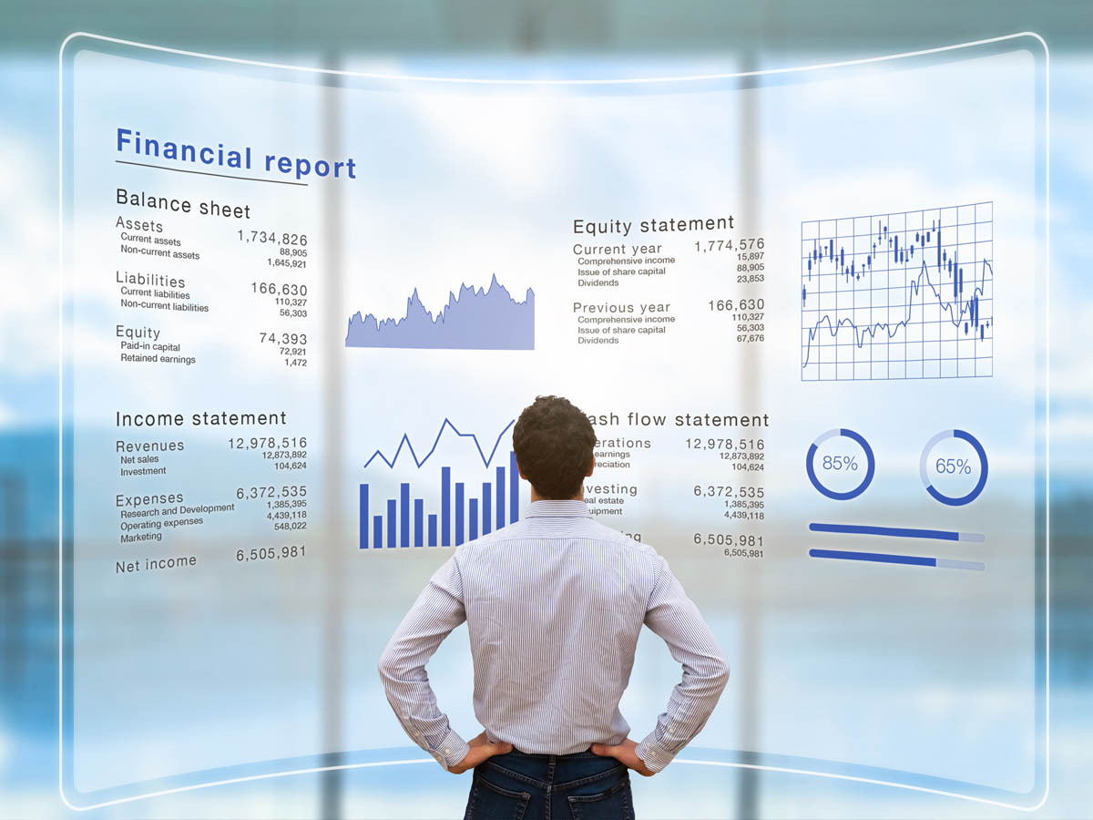 Businessman standing in front large transparent screen, analyzing the various financial data of a company operations