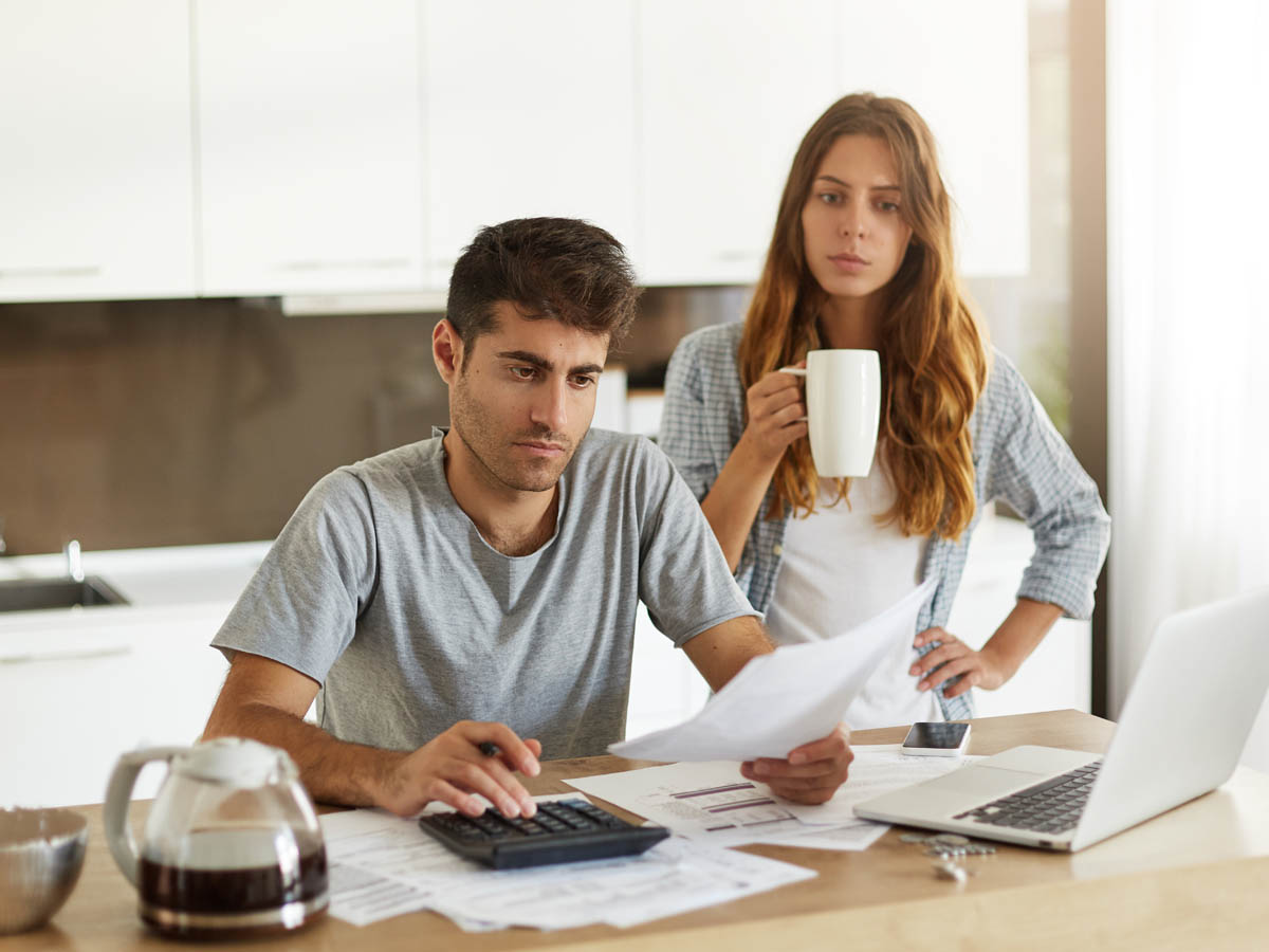 Young couple managing family budget in kitchen