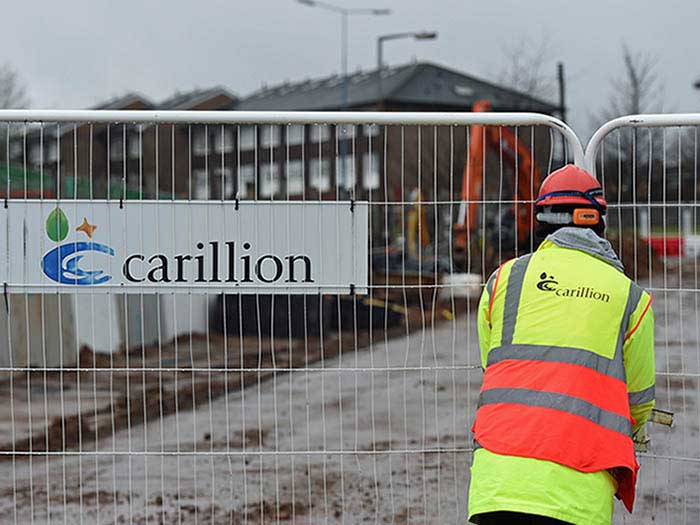worker closes gate at Carillion worksite