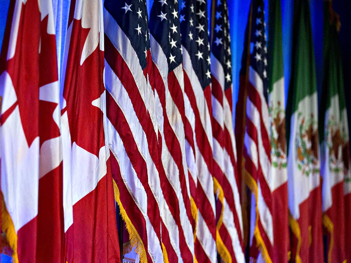 A row of flags of the three North American countries side-by-side at the NAFTA trade talks