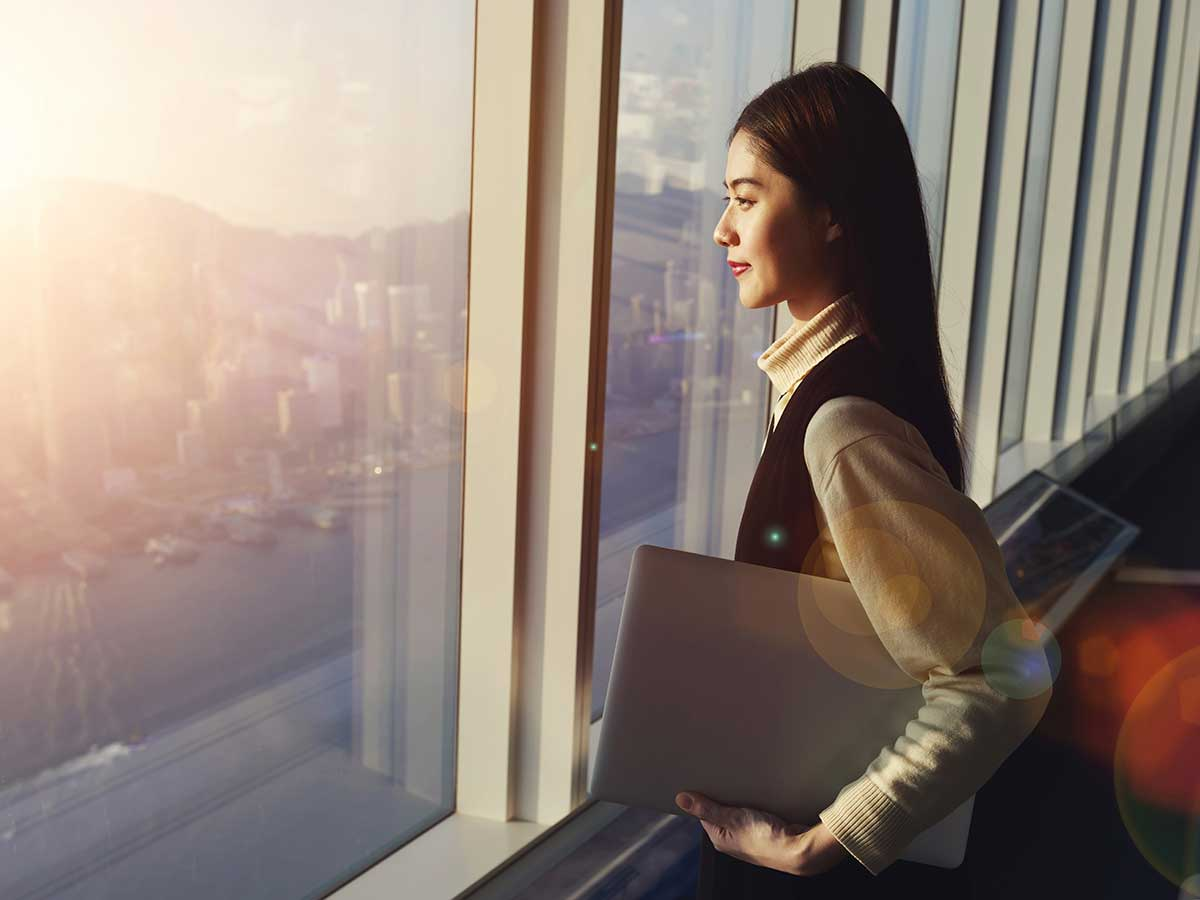 Young woman holding laptop computer, while standing in office interior and looking out of big window with city view