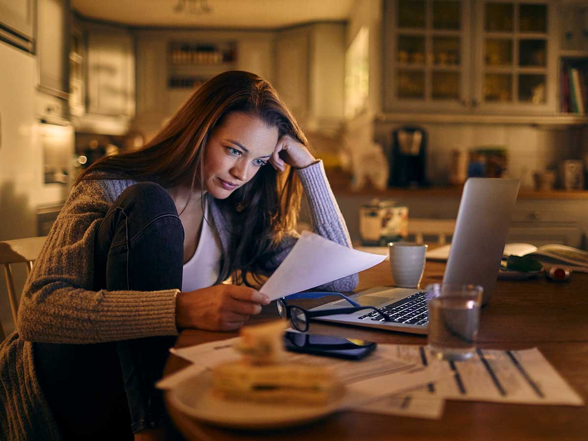 Conerned looking young woman sitting in kitchen looking over finances