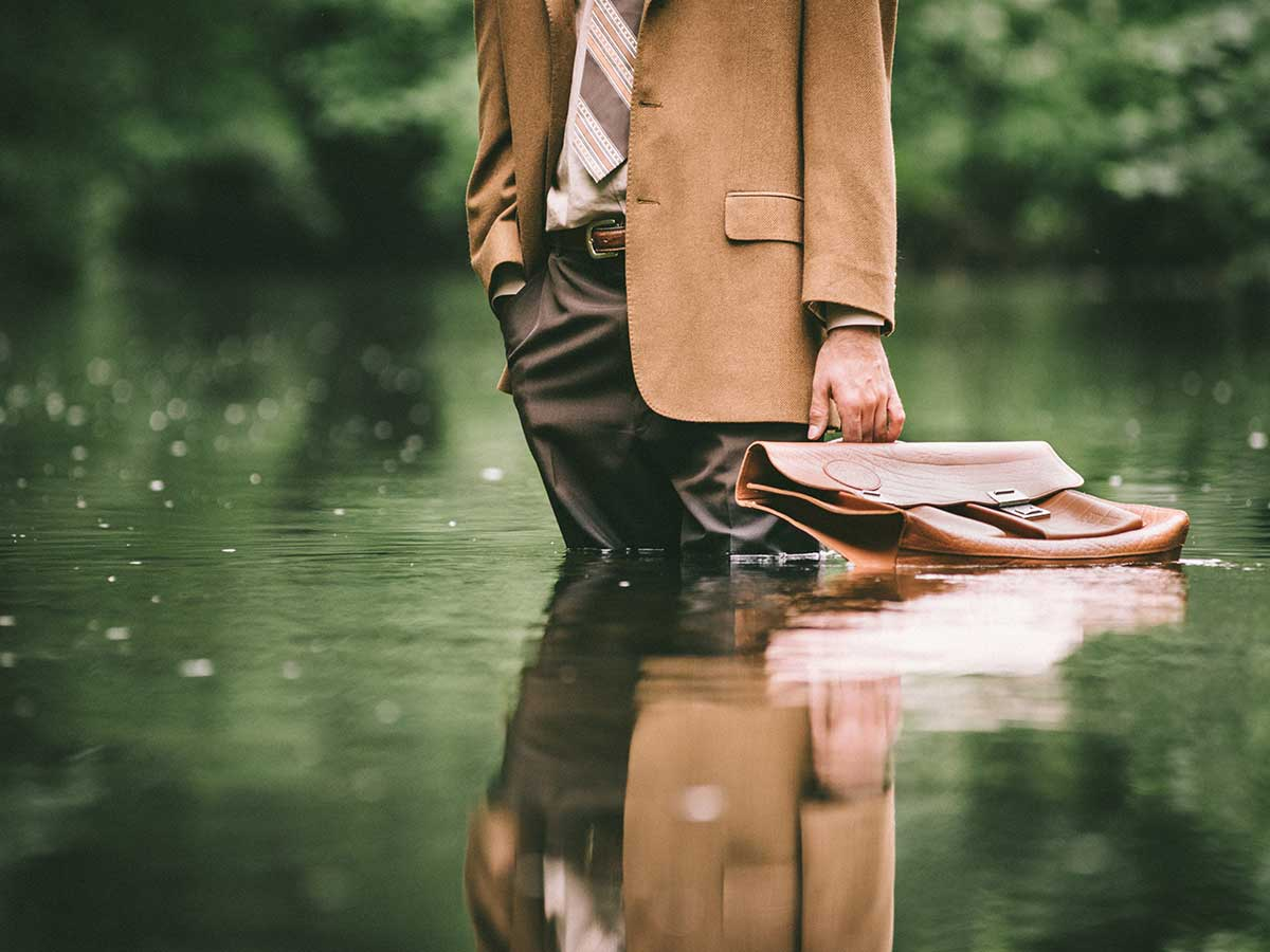 businessman with briefcase standing in a flooded area outside