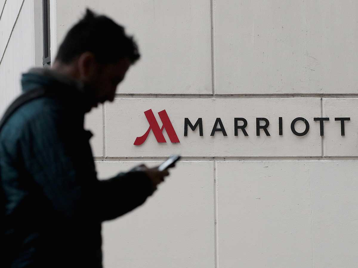 Silhouette of person on phone, in foreground, walking in front of Marriott hotel sign