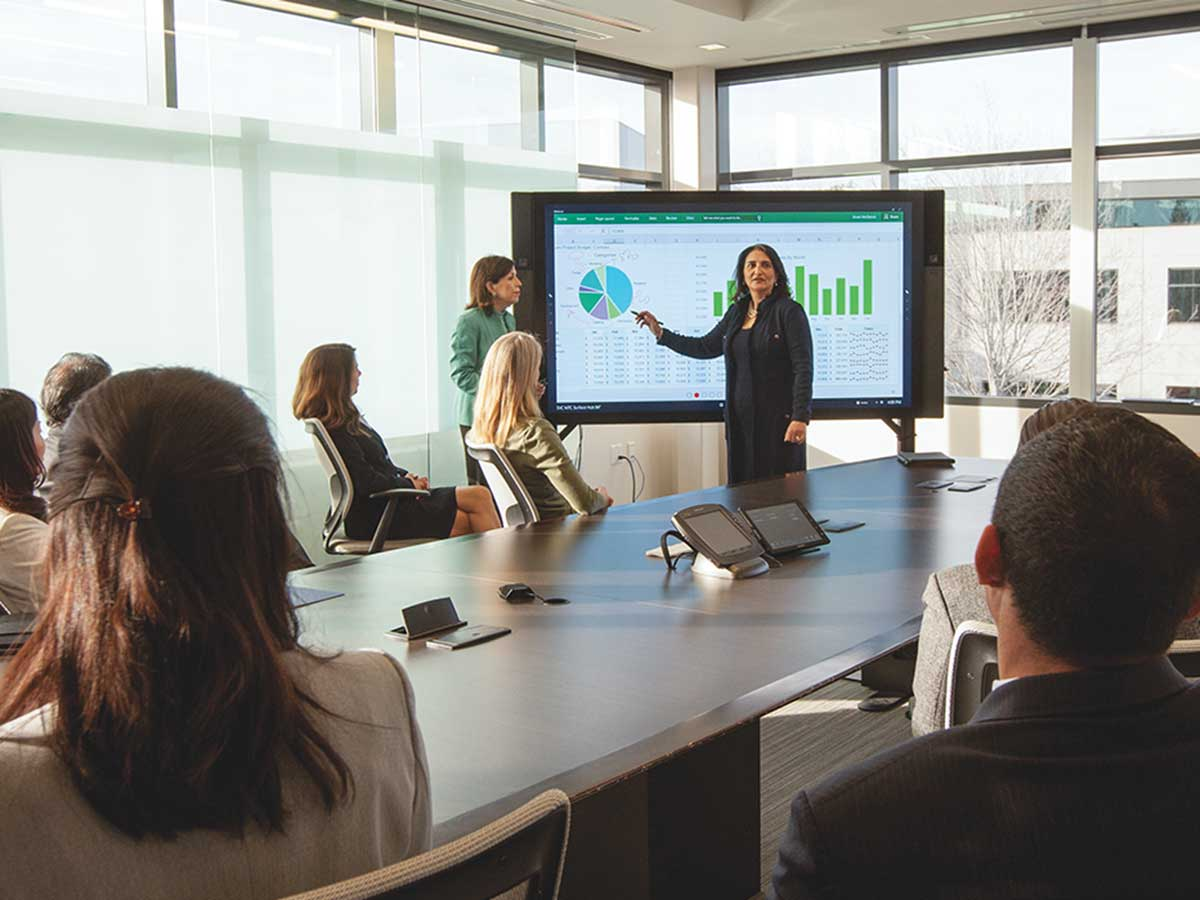 woman presenting in front of a screen in a boardroom