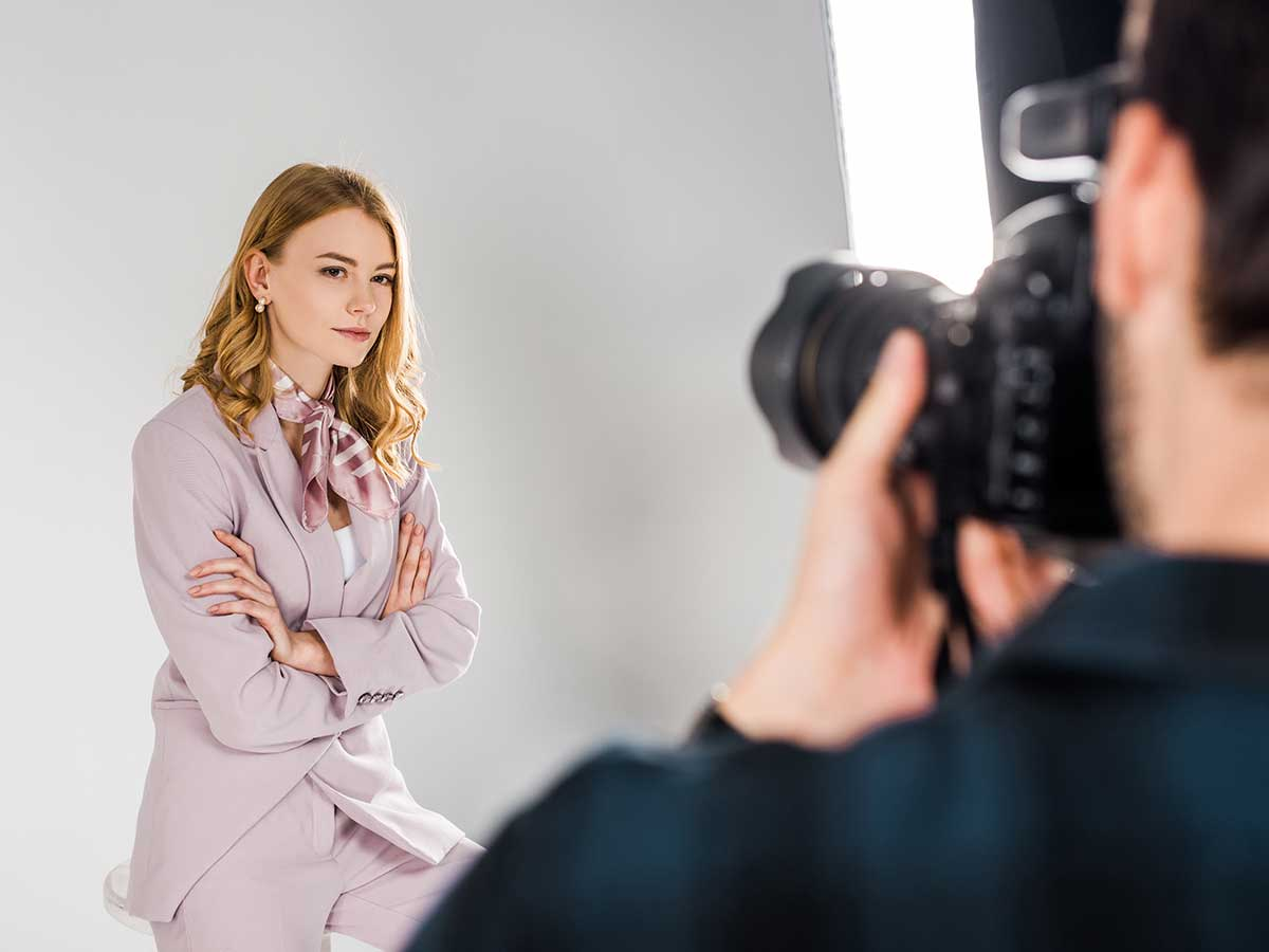 photographer shooting a young business woman in a photography studio