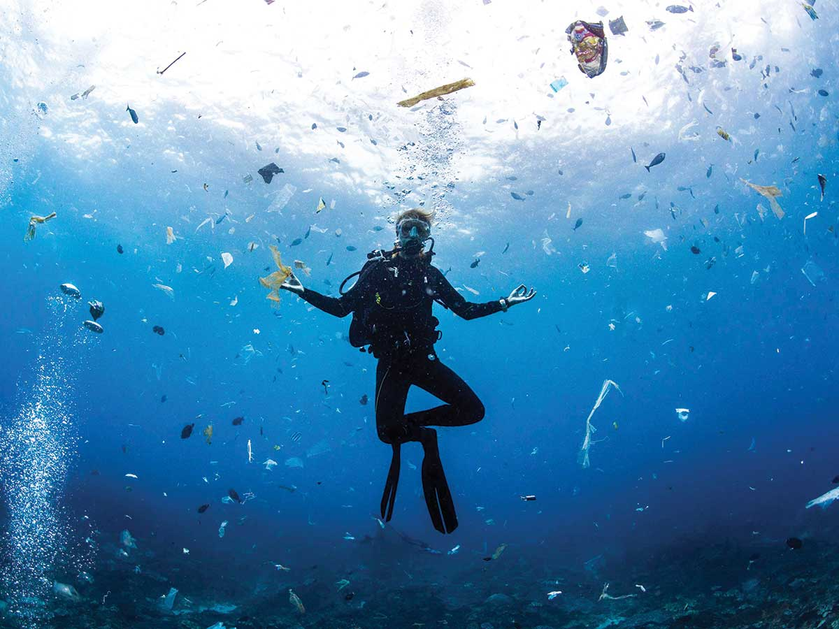 A scuba diver surrounded by plastic