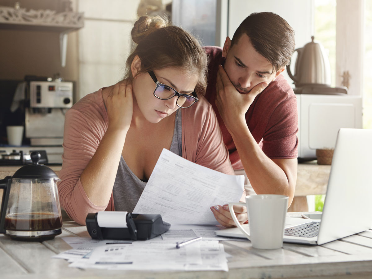 Young family having debt problems, not able to pay out their loan. Couple studying paper form bank while managing domestic budget together in kitchen
