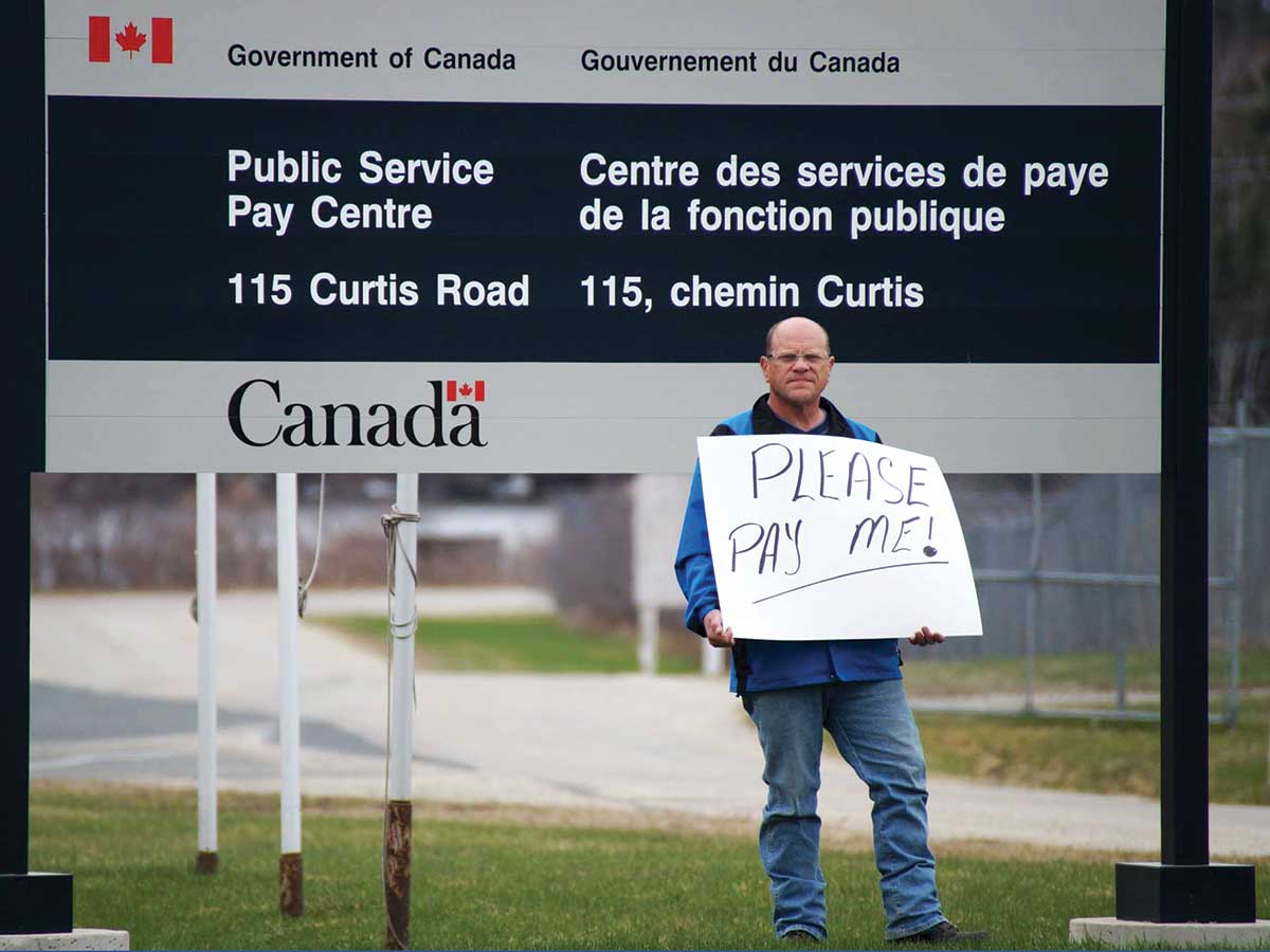 Man holding protest sign in front of government building