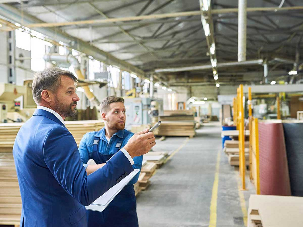Mature businessman inspecting factory warehouse with younger workman