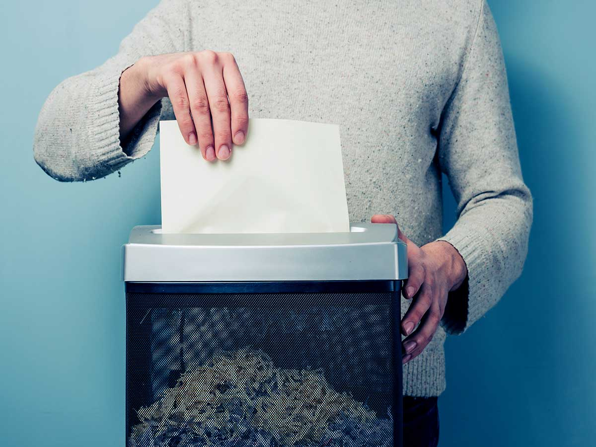 young person shredding documents, using a paper shredder