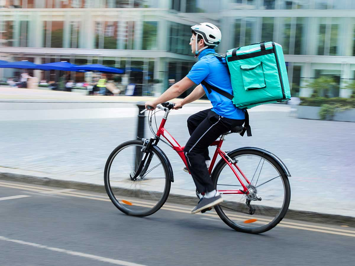 Courier on bicycle delivering food In city