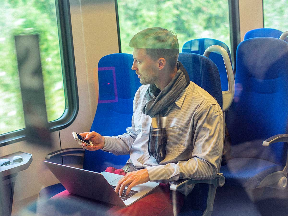 Young man on train, using smart phone and a laptop, while commuting