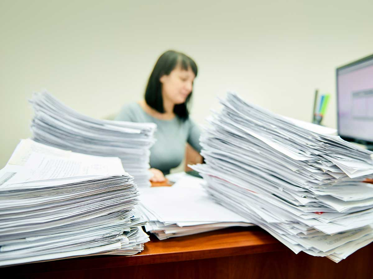 Female accountant surrounded by stacks of paper documents