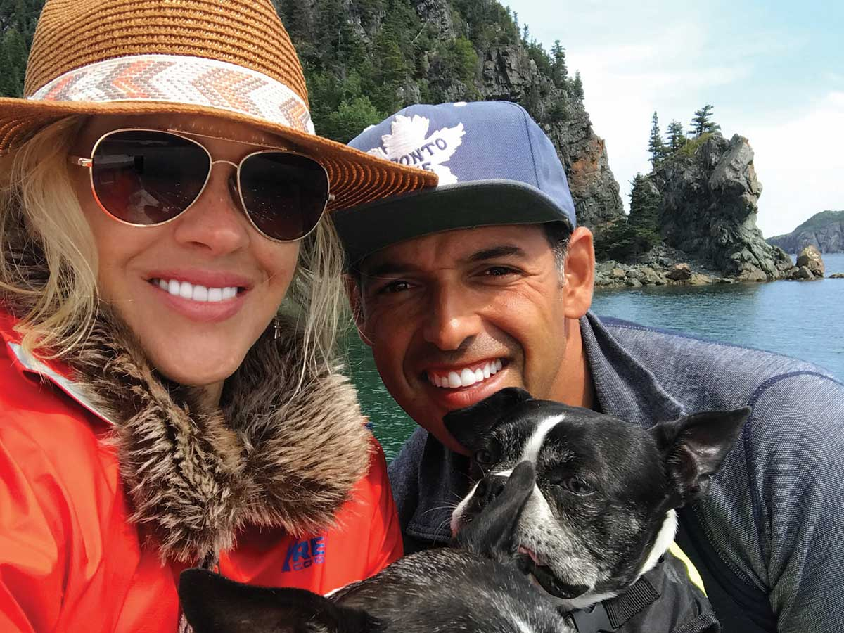Comedian Shaun Majumder and wife Shelby Fenner with their dogs by the waters of Newfoundland