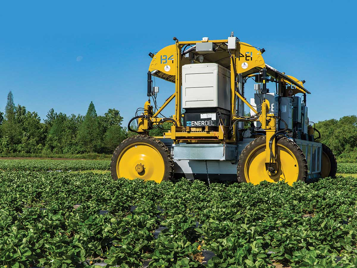 Large unmaned robot farm equipment working in farming field