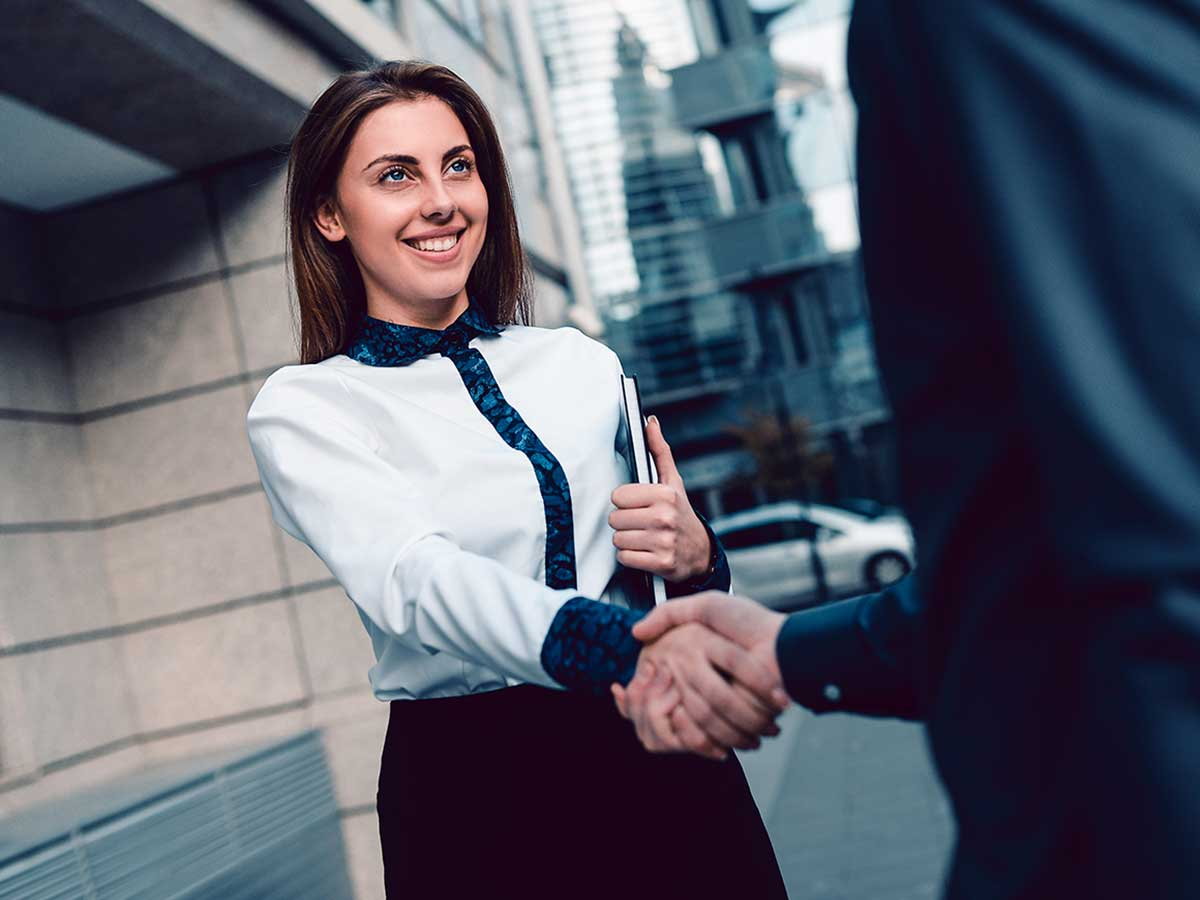 young business lady shaking hands with another business person outside a city building
