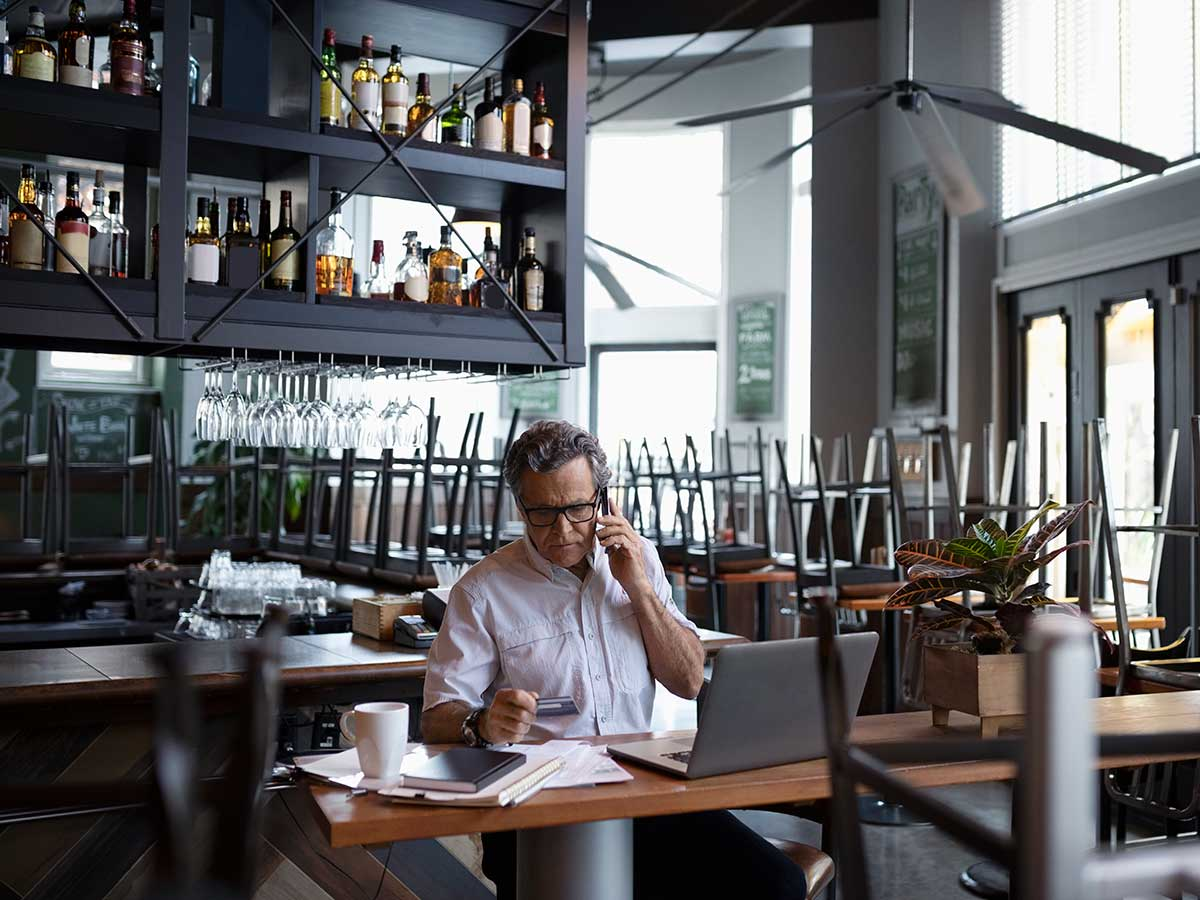 Restaurant owner doing paperwork at laptop at table after hours
