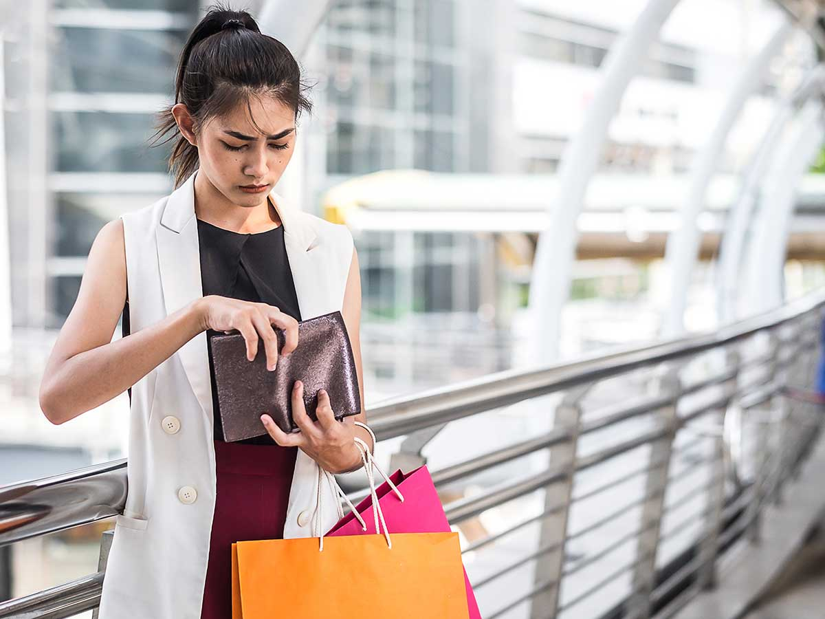 Young lady with shopping bags on her arm, looking worried that her wallet is empty