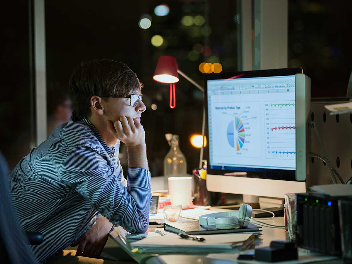 Office worker working late at night exmining business information on computer screen
