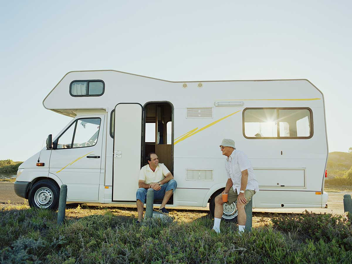 Two senior men relaxing outside their campervan with sun behind them