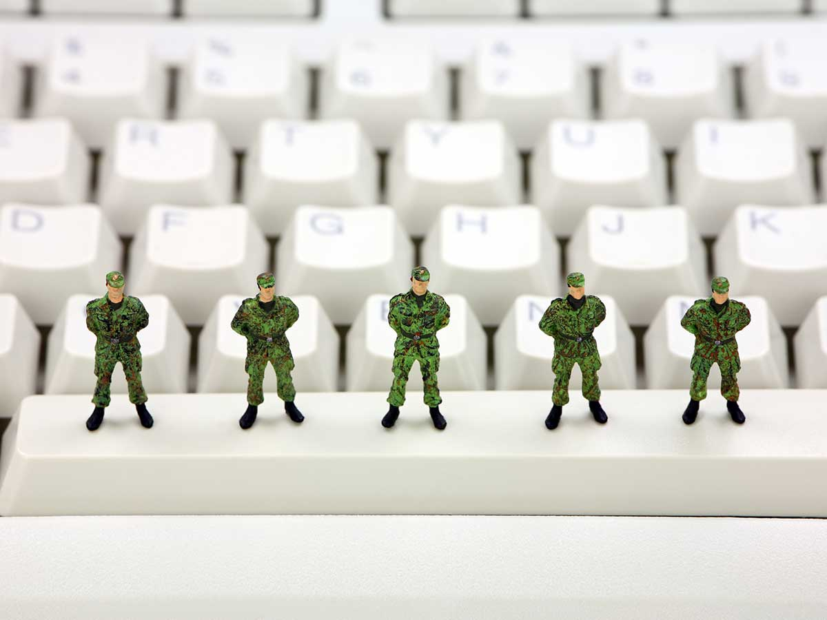Miniature toy army soldiers standing on a computer keyboard guarding against viruses, spyware and identity thieves