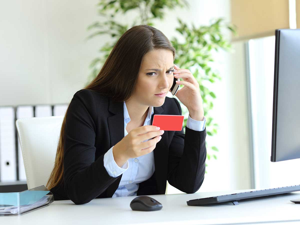 Confused business women on smart phone in her office, holding her credit card
