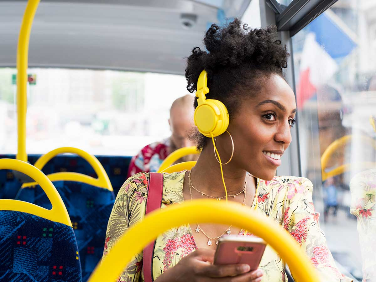 Happy young lady relaxing on a bus wearing headphones, listening to music