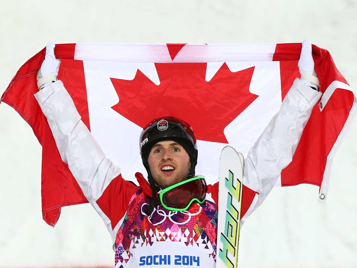 Gold medalist Alex Bilodeau of Canada celebrates during the flower ceremony for the Men's Moguls Finals on day three of the Sochi 2014 Winter Olympics
