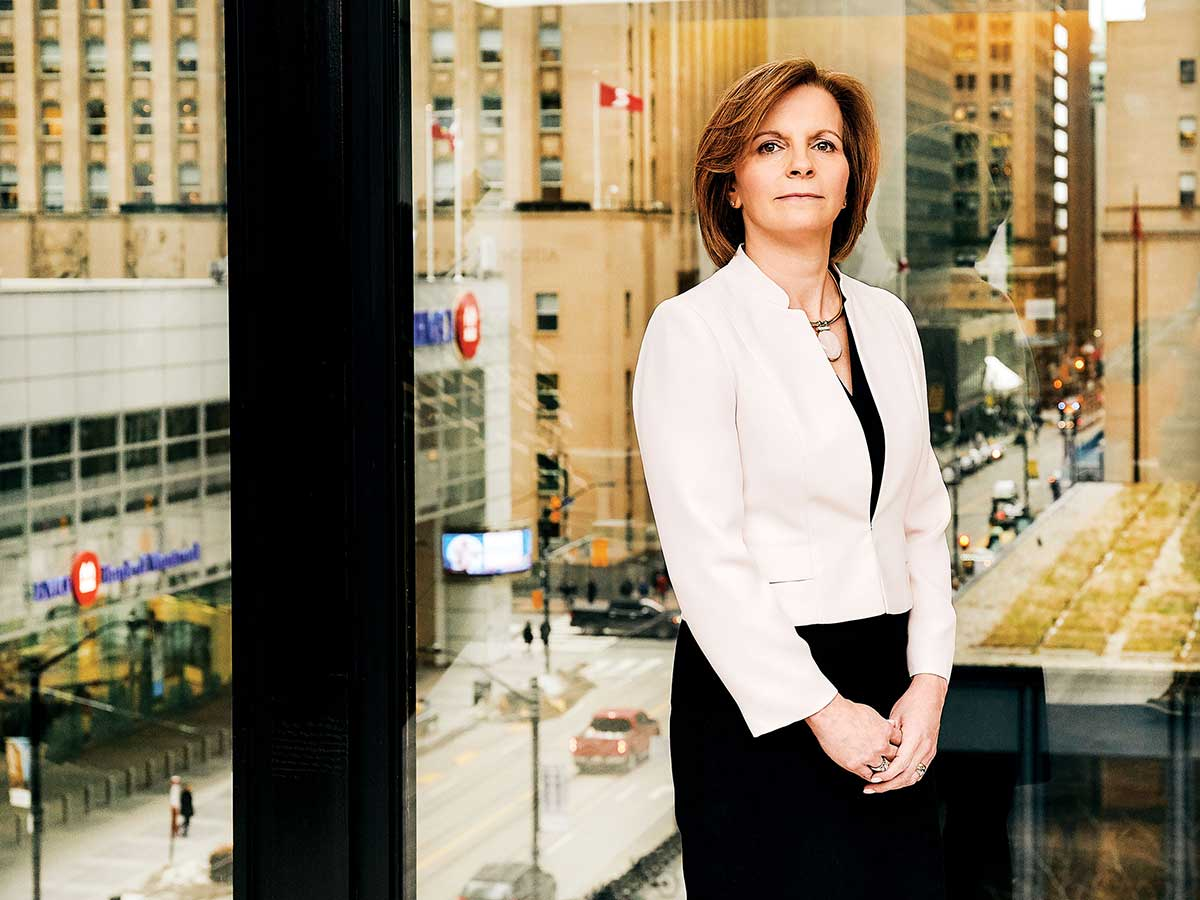 portrait of Beth Wilson standing in window of the Dentons Canada office in Toronto's Financial District
