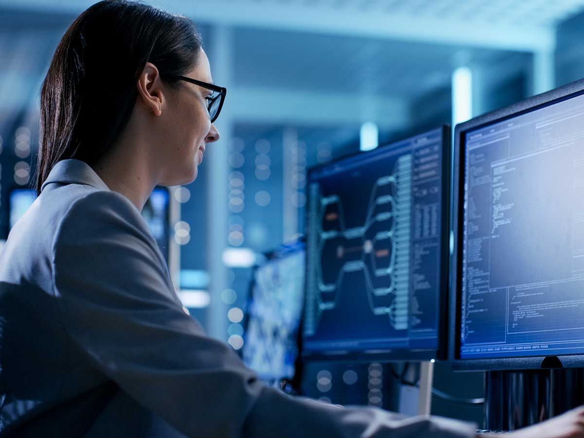 Woman at computer in a room full of servers, checking data on screen