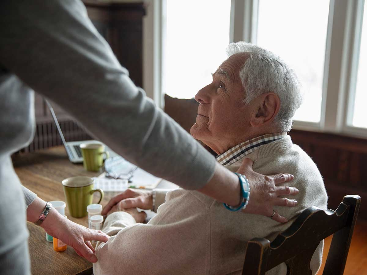 caregiver comforting senior man at table in his home