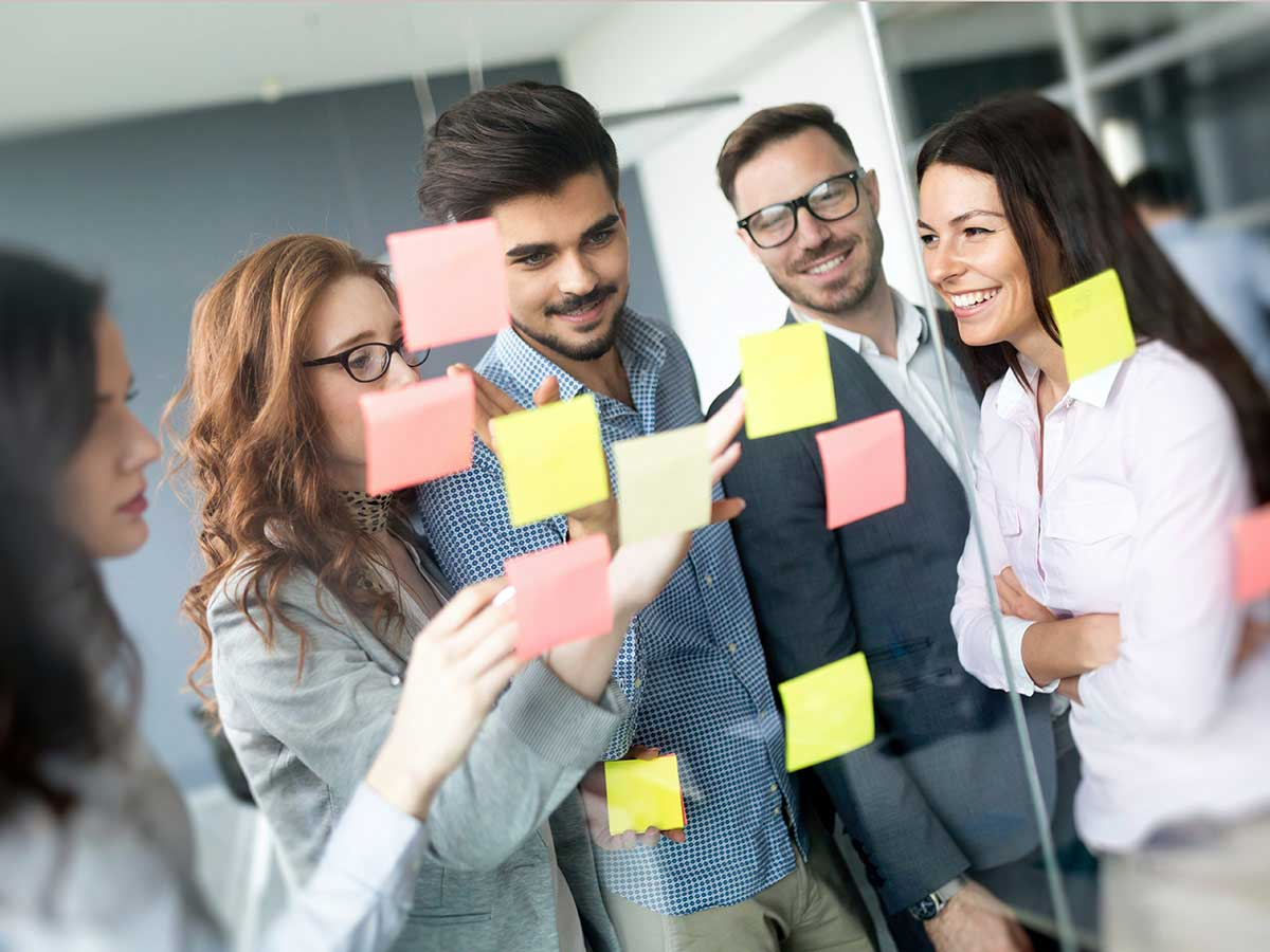 Young business people using post-it notes in a brainstorming meeting