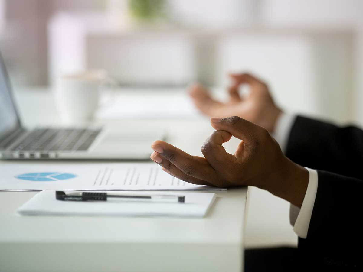 Close up of the hands of a African american businessman in mudra position, relaxing and meditating at work desk in an office