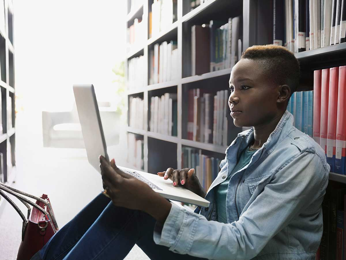 Young lady using laptop between library bookshelves to study