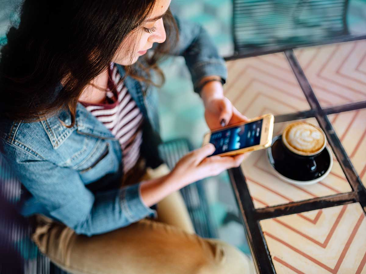 Young woman using smart device to check finances at a coffee shop