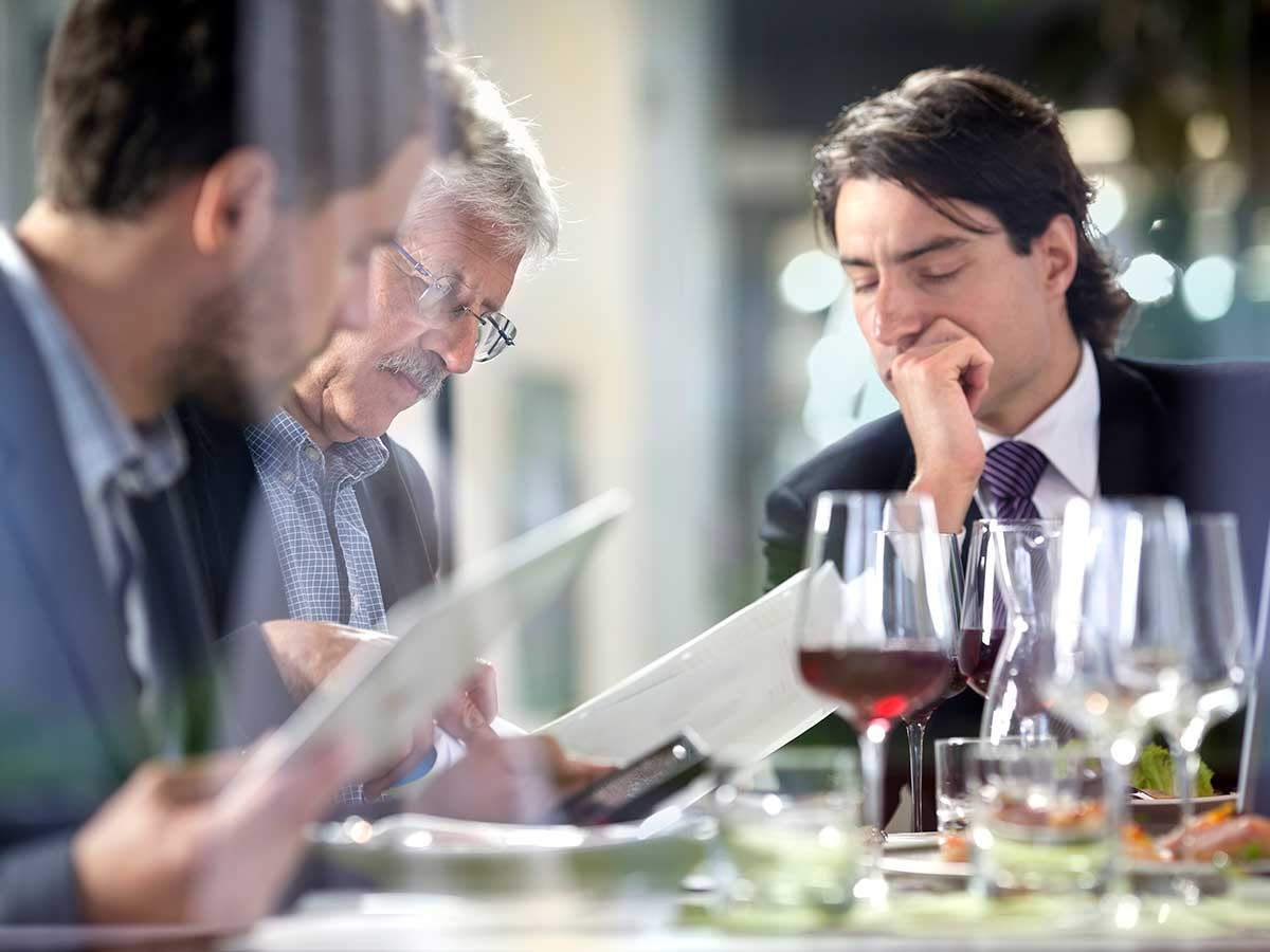Business people having lunch at restaurant while studying business paperwork