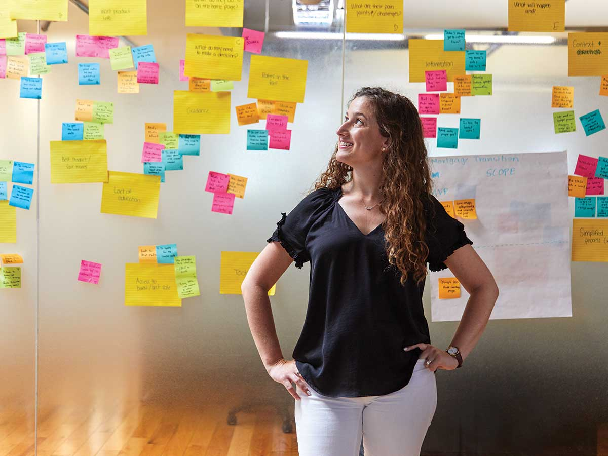 Portrait of Jennifer Pollock, Ratehub's director of finance and operations, in front of a glass wall with Post-it notes