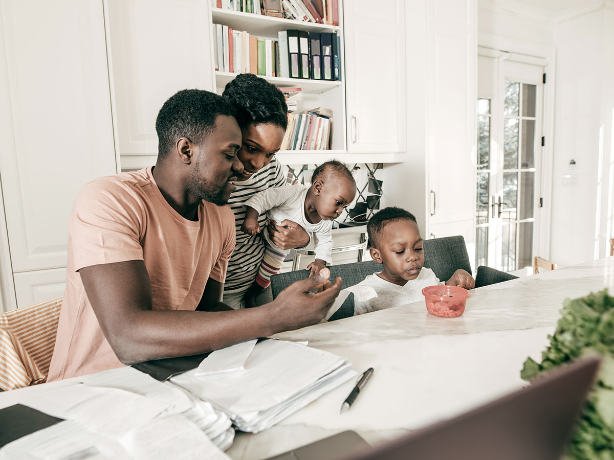 couple and their children hanging out in the kitchen, while looking at financials on a laptop