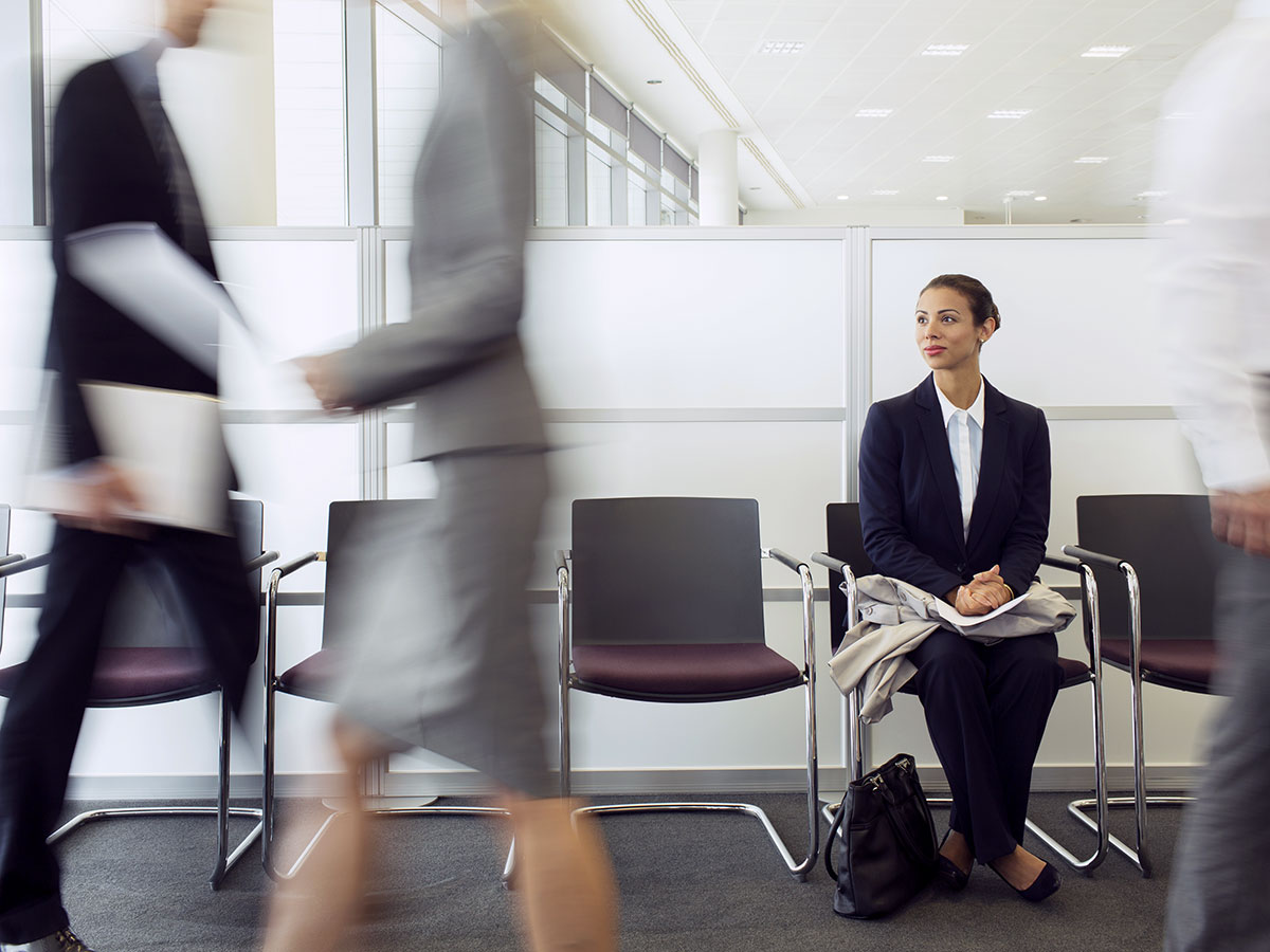 young business woman, sitting in waiting area, while employees move about the office